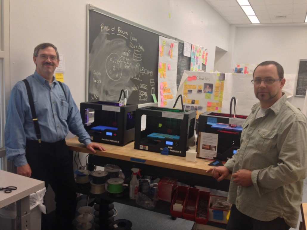 Andrew Bennett and John Graham in front of 3-D printers at work